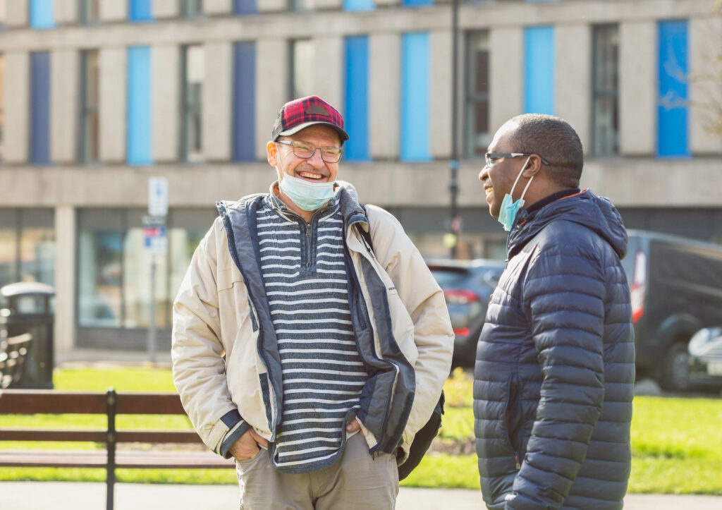 Nicky Auguste and Jan, a BDP service user, sharing a laugh outside
